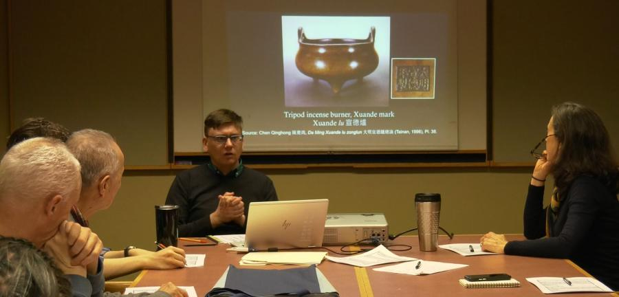 photo of colloquium session people with slide of incense burner in the background