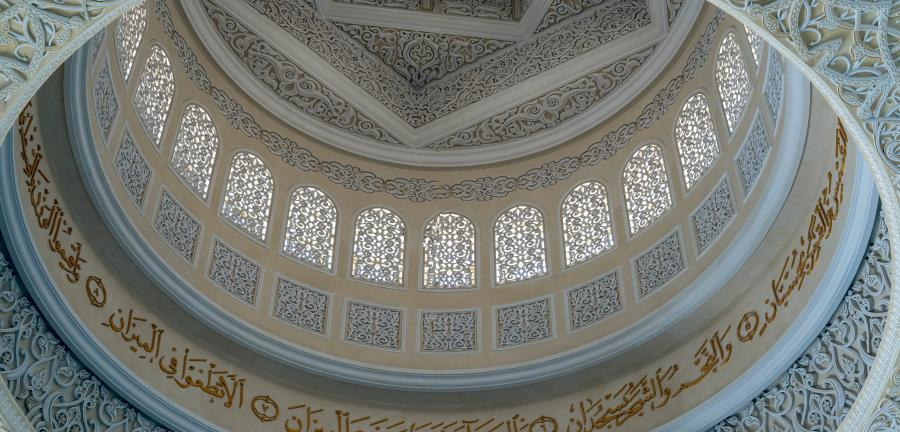 Interior dome of a mosque covered in calligraphy