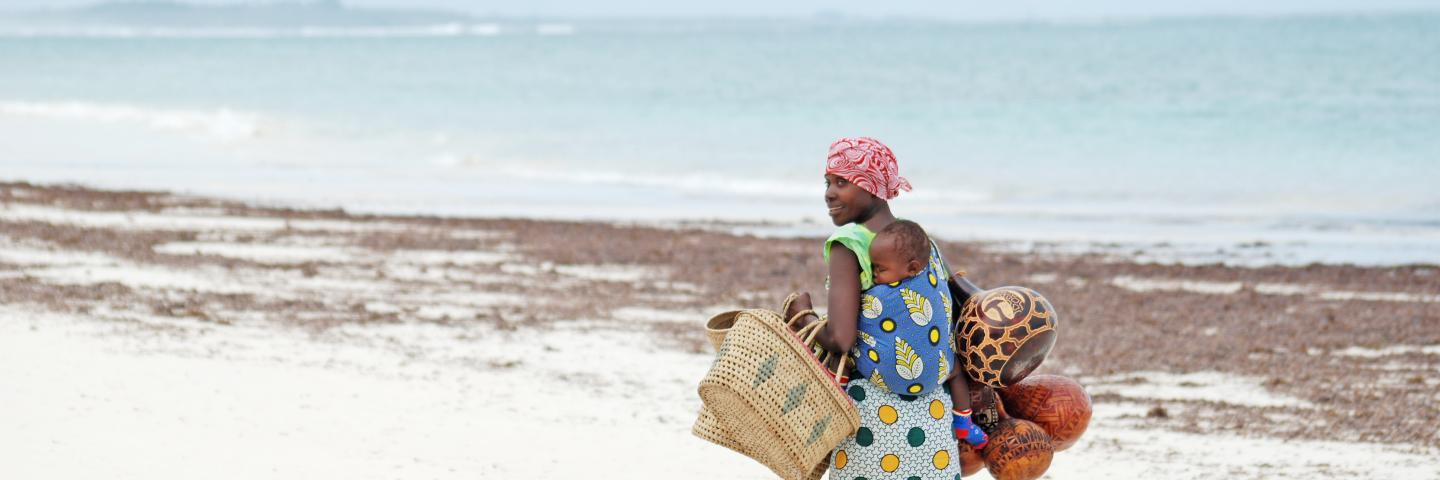 African woman with child walking on beach