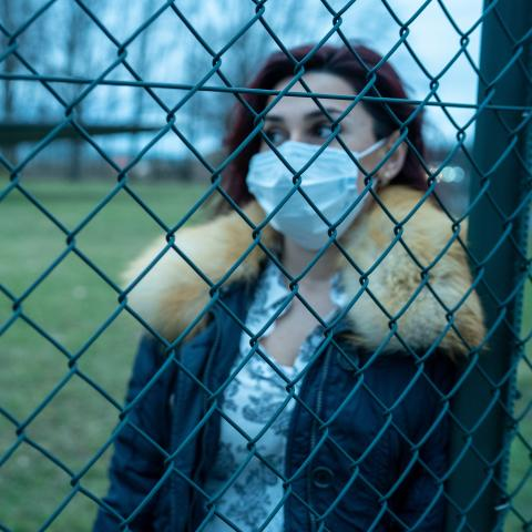 Woman wearing mask behind chainlink fence